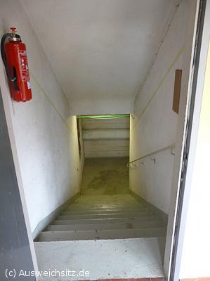 """Abstieg in den verbunkerten und bisher unbekannten Teil des Hochwald-Gymnasiums. Neben der Treppe hängt ein Hinweisschild """"zum Werkraum""""."""