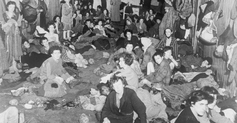 Das Foto zeigt Frauen und Kinder bei der Befreiung von Bergen Belsen - draußen türmten sich die Leichenberge. Foto: Imperial War Museum / Wikimedia Commons