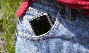 Aus einer Hosentasche ragendes Mobiltelefon
