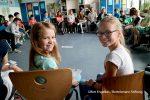Schüler sitzen im Stuhlkreis in einem Klassenraum. Im Vordergrund sind zwei Schülerinnen zu sehen, die sich zur Kamera hin umgedreht haben und lächeln. Gewinner des Jakob Muth-Preises für inklusive Schule.