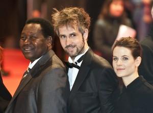 Filmemacher Gaston Kaboré, Regisseur Christoph Schlingensief und Bühnenbildnerin Aino Laberenz bei der Eröffnung der Berlinale 2009. (Foto: Sibbi/Wikimedia CC BY 3.0)