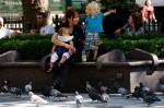 Tagesmutter mit zwei Kindern auf einer Parkbank