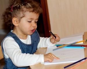 kleines Mädchen mit Buntstiften an einem Zeichentisch
