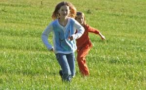auf einer Wiese laufen 2 Kinder