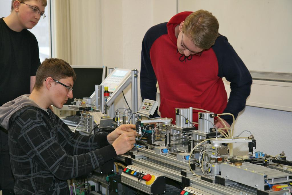 Berufsschüler an einer Maschine