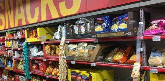 Es gibt viele Snacks im Supermarktregal und die Konkurrenz ist hart. Werbung ist da von großer Bedeutung für die Hersteller. Foto (Extra (Coop supermarket) Bergen Storsenter Norway 2017-11-16 snacks aisle): Wolfmann / Wikimedia Commons (CC BY-SA 4.0) (Ausschnitt mit verwischten Schriftzügen)